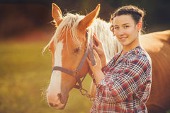 Portrait beautiful woman next horse in warm summer sunny day Stock Photo