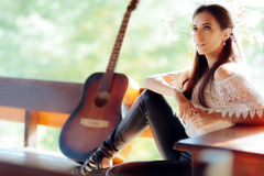 Portrait of a Beautiful Woman next to Her Guitar Stock Image