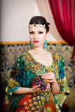 Portrait of a beautiful woman in oriental dress. Grace and beauty. Royalty Free Stock Photos