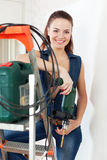 Portrait of beautiful woman in overalls with drill stock image