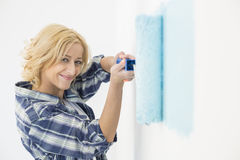 Portrait of beautiful woman painting wall with paint roller Stock Image