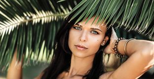 Portrait of a beautiful woman in palm leaves Royalty Free Stock Photo