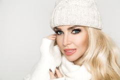 Portrait of beautiful woman with perfect face in winter cap and warm sweter. The model presents winter clothing Royalty Free Stock Photos