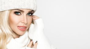Portrait of beautiful woman with perfect face in winter cap and warm sweter. The model presents winter clothing Stock Photo