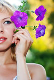Portrait of beautiful woman with petunia. About face Stock Photo
