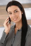 Portrait of beautiful woman on phone smiling. Portrait of beautiful young businesswoman talking on mobile phone, smiling Royalty Free Stock Images