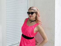 Portrait of beautiful woman in pink dress by the wall stock photo