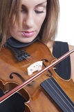 Portrait of a beautiful woman playing violin. A close up of a beautiful woman playing the violin set against a white background Royalty Free Stock Photo