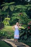 Portrait of beautiful woman posing among blooming asian flowers on Bali island, Indonesia. Stock Image