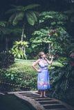 Portrait of beautiful woman posing among blooming asian flowers on Bali island, Indonesia. Stock Photography