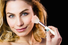 Portrait of beautiful woman posing with make-up brush Royalty Free Stock Photo