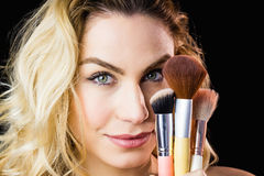 Portrait of beautiful woman posing with make-up brush Stock Images