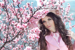 Portrait of Beautiful woman posing over Pink Spring Cherry bloss Stock Image