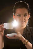 Portrait of beautiful woman posing in studio with cup of coffe. Portrait of sexy woman posing on black background with cup of coffe Stock Image