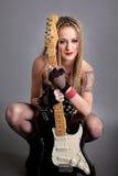 Portrait of beautiful woman punk rocker holding guitar Royalty Free Stock Photos