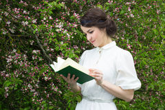 Portrait of beautiful woman reading book in blooming spring gard Stock Photography