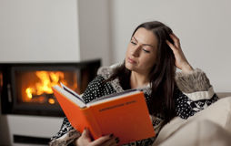 Portrait of beautiful woman reading book by fireplace Royalty Free Stock Image