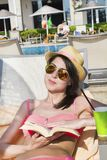 Portrait of Beautiful Woman Reading Book on the Pool. Reading a book on the beach .summer sea vacation Stock Images