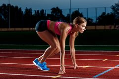 Portrait of beautiful woman ready to start running. Female athlete sprinter doing a fast sprint for competition on red lane at an outdoor field stadium Royalty Free Stock Photography