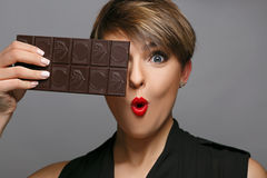 Portrait of a beautiful woman  that is a real chocolate fan on a grey background. Stock Image