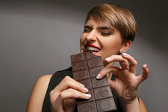 Portrait of a beautiful woman  that is a real chocolate fan on a grey background. Stock Photos