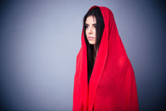 Portrait of a beautiful woman in red cloth. Looking away. Standing over gray background Stock Photography