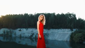 Portrait of a beautiful woman in a red dress on a mountain near. The river Royalty Free Stock Photos
