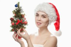 Portrait of a beautiful woman in a red hat and with a Christmas tree with christmas balls and red bows. stock photo