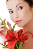 Portrait of beautiful woman with red lily flower. Royalty Free Stock Photos