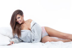 Portrait of beautiful woman relaxing on bed. Conceptual photo of smiling beautiful brunette woman lying in bed, relaxing at the morning Stock Image