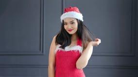 Portrait of beautiful woman Santa Claus wearing hat smiling and looking at camera medium shot. Young Asian female posing at studio enjoying and playing with