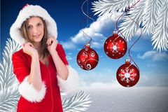 Portrait of beautiful woman in santa costume against digitally generated background Royalty Free Stock Photo