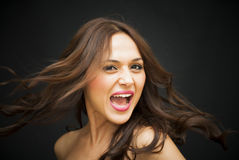 Portrait of a beautiful woman screaming. On black background Stock Image