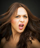 Portrait of a beautiful woman screaming. On black background Royalty Free Stock Photography