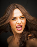 Portrait of a beautiful woman screaming. On black background Stock Photos
