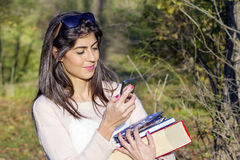 Portrait of a beautiful woman sending messages  in the park. Portrait of a beautiful  woman with book and wallet in the hands ,talking on the phone Royalty Free Stock Photos