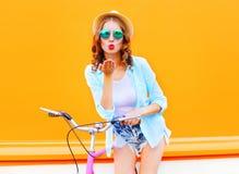 Portrait beautiful woman sends an air kiss near bicycle Stock Photo