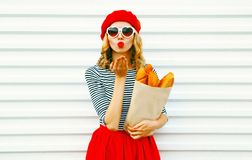 Portrait beautiful woman sends sweet air kiss wearing red beret holding paper bag with long white bread baguette. On white wall background stock images