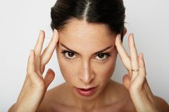 Portrait of Beautiful woman with a severe headache with the hands in the head over white empty wall on background. Beauty and healthcare concept stock images