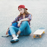 Portrait of a beautiful woman in a shirt and a baseball cap with. A skateboard in the park Royalty Free Stock Photo