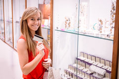 Portrait of beautiful woman showing her credit card in a jeweler shop Stock Images