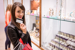 Portrait of beautiful woman showing her credit card in a jeweler shop Royalty Free Stock Photo