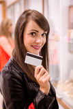 Portrait of beautiful woman showing her credit card in a jeweler shop Royalty Free Stock Photography