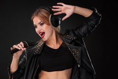 Portrait of a beautiful woman singing into Stock Photography