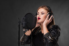 Portrait of a beautiful woman singing into Stock Images
