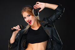 Portrait of a beautiful woman singing into microphone with headphones Stock Images