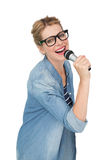 Portrait of beautiful woman singing into a microphone Stock Photography