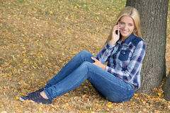 Portrait of beautiful woman sitting in autumn park with phone Stock Image