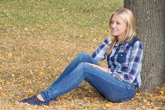 Portrait of beautiful woman sitting in autumn park Stock Image