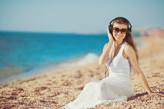 Portrait of beautiful woman sitting on the beach near the sea in headphones listening to music Royalty Free Stock Photos